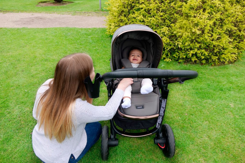 Haley is crouched next to the pushchair while baby Elodie lies in the seat with the hood up.