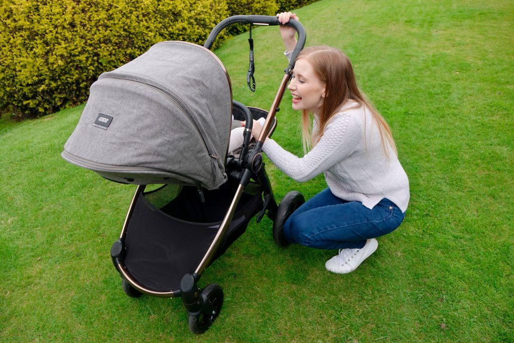 Haley is crouched next to the Ocarro pushchair, talking to baby Elodie. She is in a park, on the grass.
