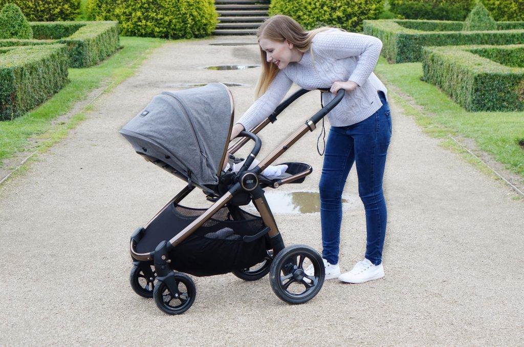 Haley is pushing baby Elodie in the Ocarro pushchair along a gravel path. She is leaning in to the pushchair to reassure the baby.