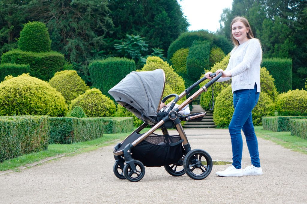 Haley is posing with the Ocarro pushchair is a park with bushes, hedges and topiary displays behind her.