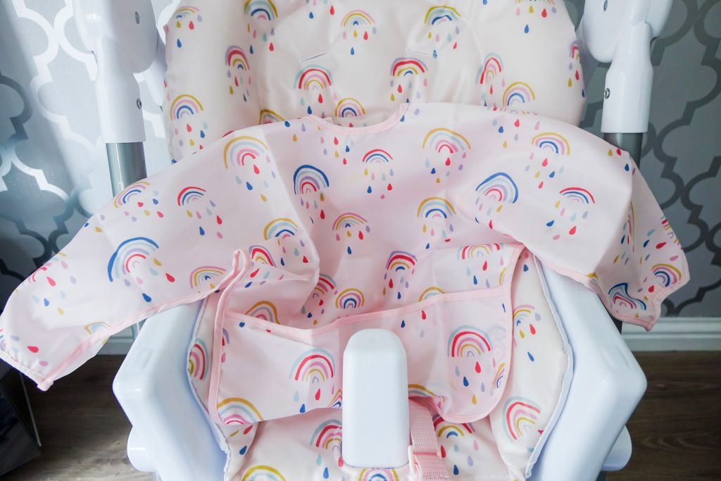 Close up of rainbow themed padded seat cover and coordinating bib.
