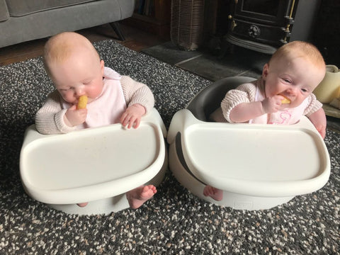 The young twin girls, Esther and Eve, are sat in their Baby Snug booster seats and are both chewing on a piece of food.