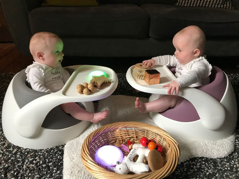 The twin babies, Esther and Eve, are sat in their Baby Snug booster seats and have been positioned to face each other.