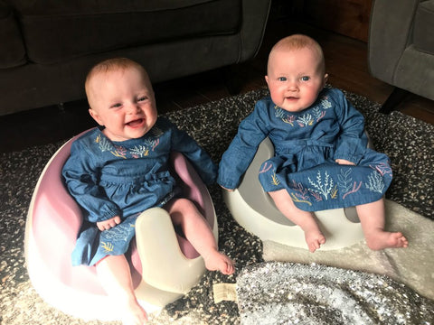 Twin girls, Esther and Eve are wearing matching denim dresses and are sat on the floor in their Baby Snug booster seats.