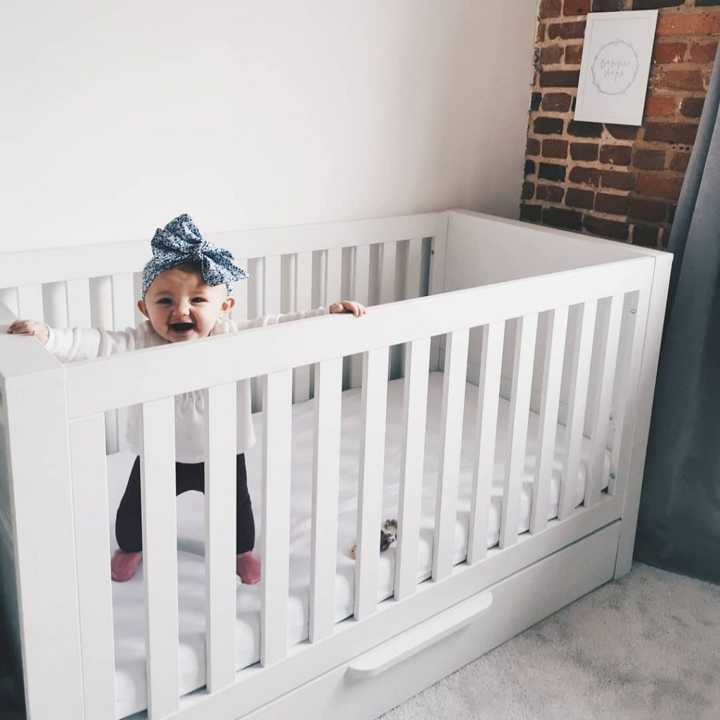 Image of baby Bonnie standing up tall in the Franklin cot bed