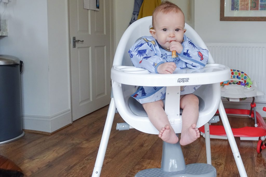 Baby Marlow is sat in the Bop highchair, wearing a long sleeved bib and eating some food.
