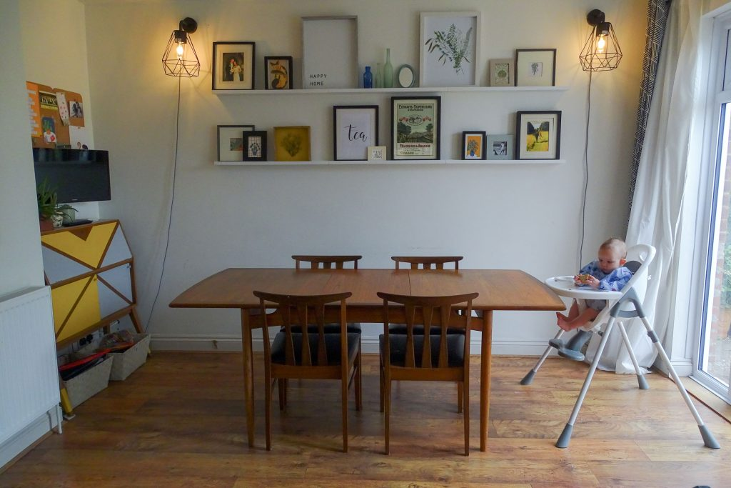 Image of a dining room with dining table, at one end is baby Marlow in the highchair.