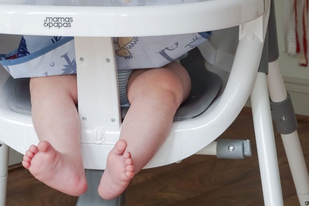 Close up of the Bop highchair seat, with baby's Marlow's legs hanging down.
