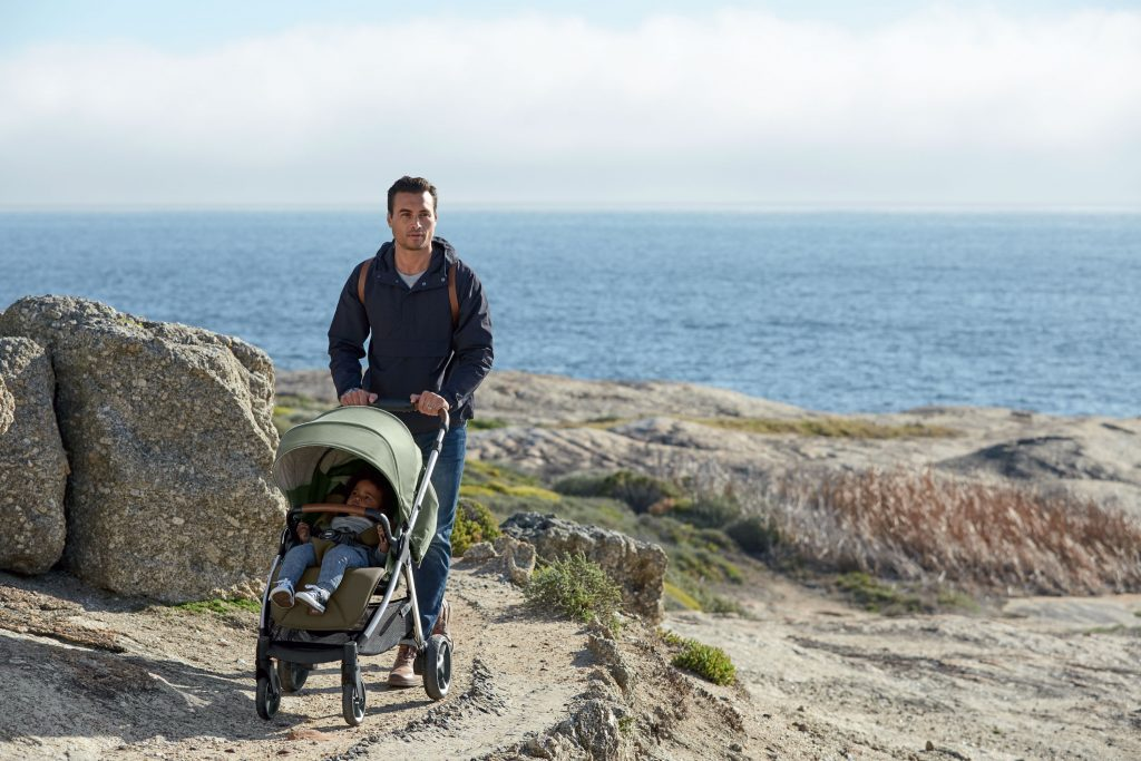 A father pushes his child in an Armadillo XT pushchair along a mountain cliff top, overlooking the sea.