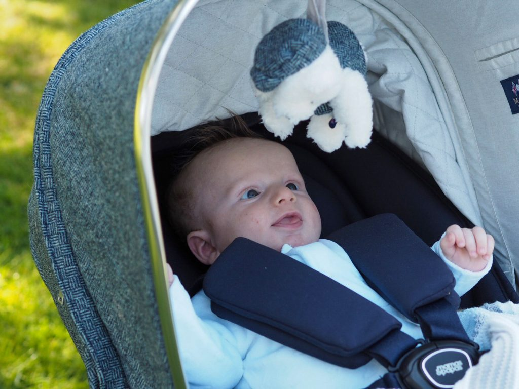 Image of baby Freddie sat in the Ocarro pushchair, wide awake looking at a soft toy that's hanging down from the pushchair hood.
