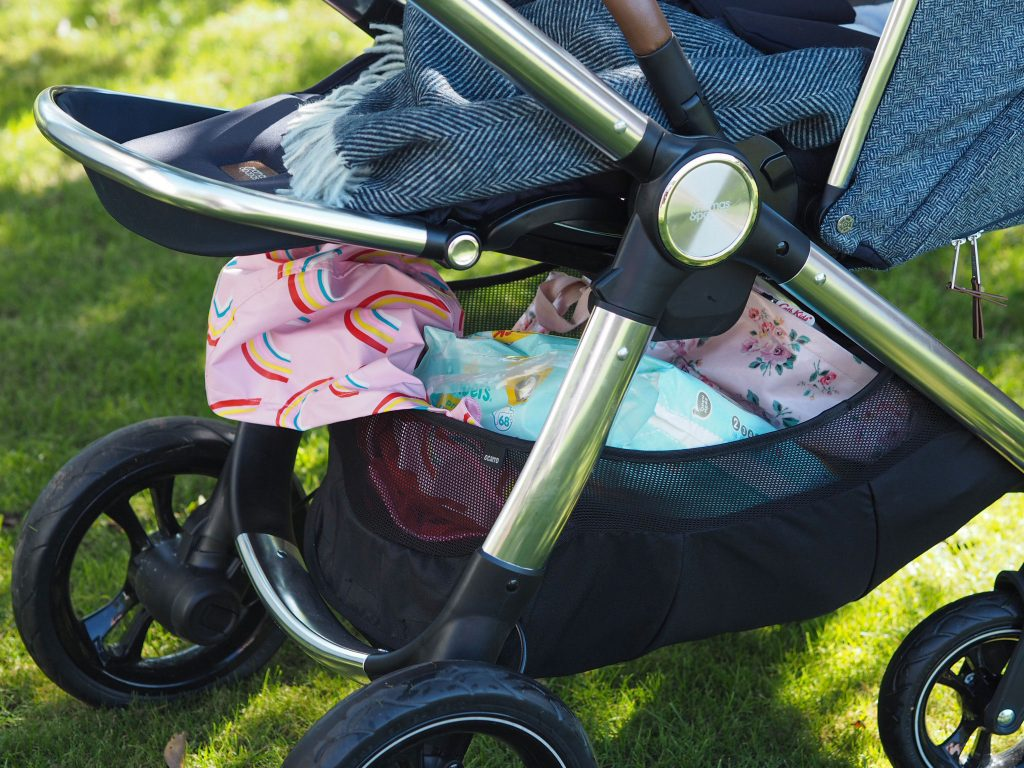 Close up of the Ocarro moon pushchair and the large shopping basket under the seat. It is full of coats and clothes and other accessories.