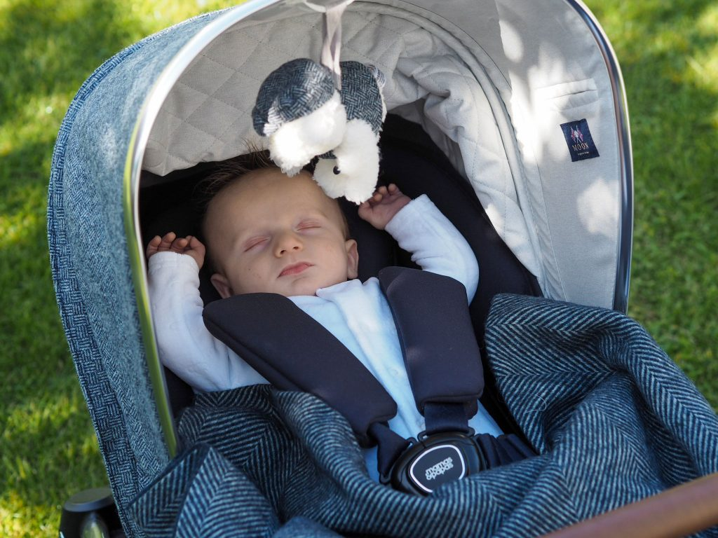 Image of baby Freddie in the Ocarro Moon pushchair asleep. The pushchair hood is pulled up and a soft toy hangs down above him.