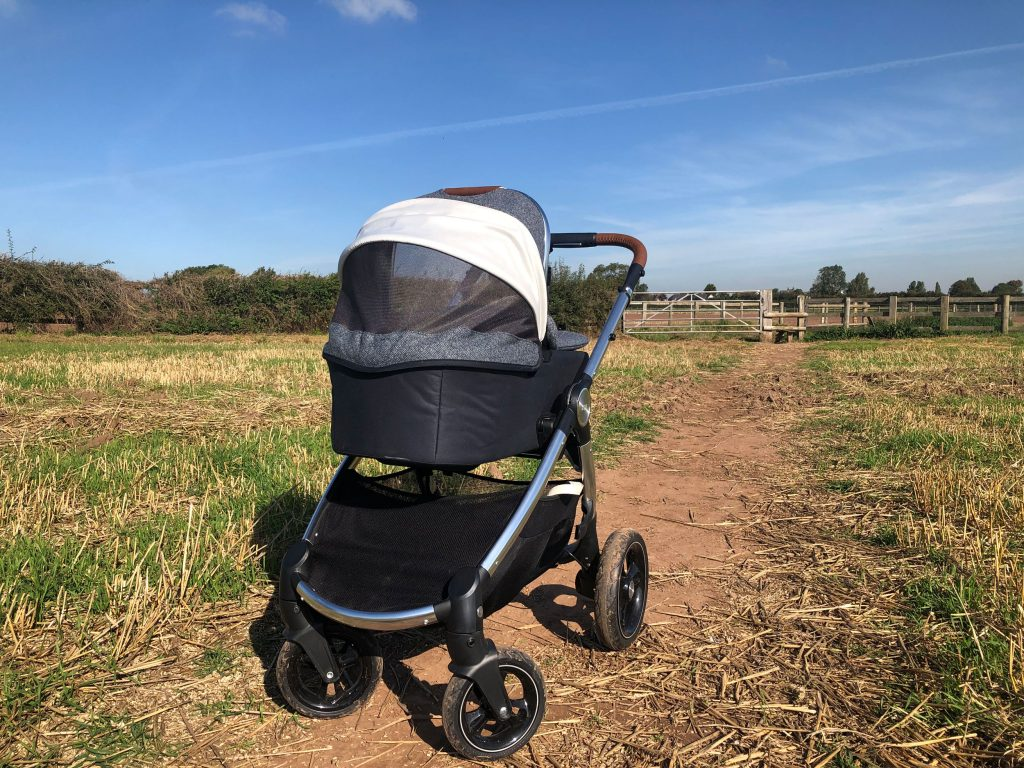 Image of the Ocarro Moon pushchair on a dirt track in the middle of a field.