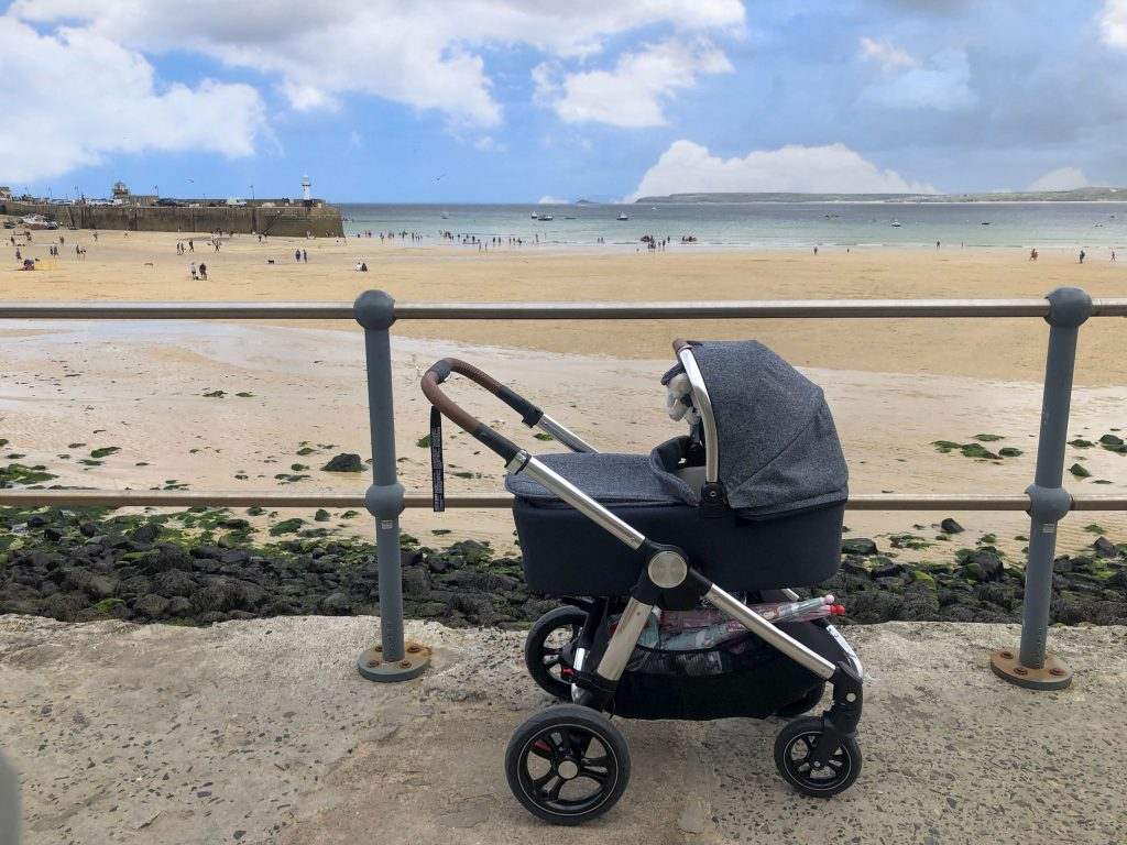 Image of the Ocarro Moon pushchair on a pavement overlooking a sunny beach.