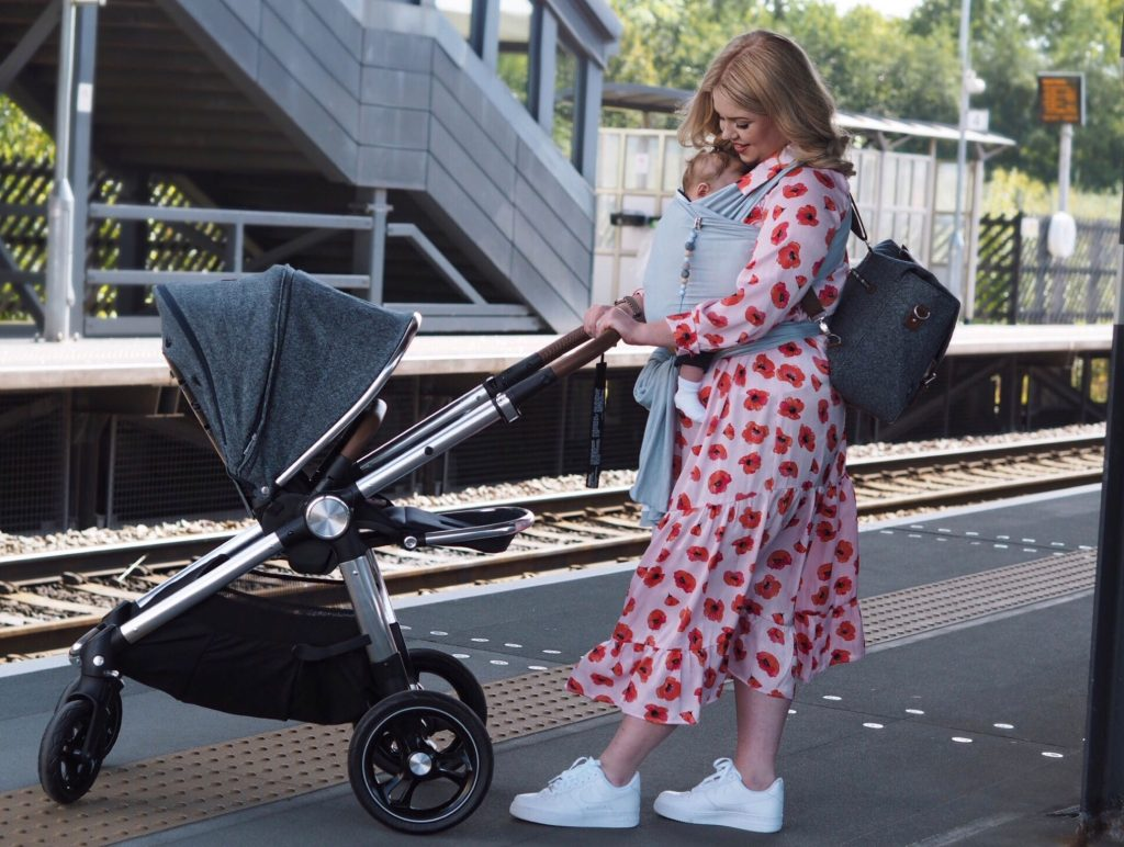 Image of Harley on a train station platform pushing the Ocarro Moon pushchair, while baby Freddie is fast asleep in a baby carrier strapped to Harley's chest.