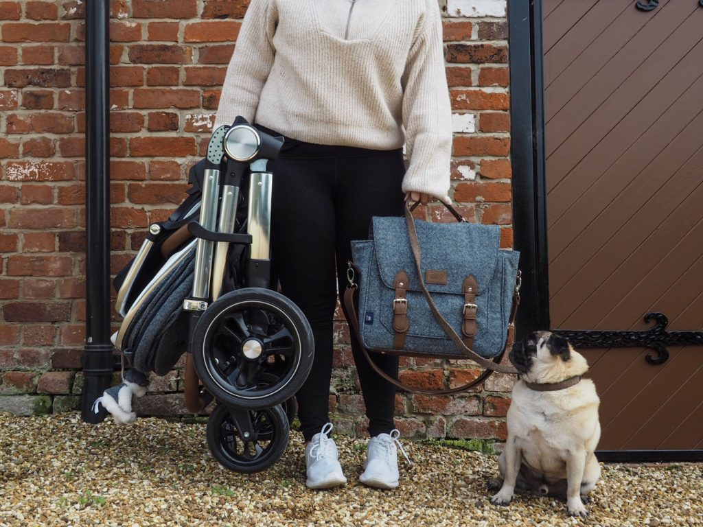Image of Harley holding the Ocarro pushchair, which is folded up into a compact size, and a matching changing bag.