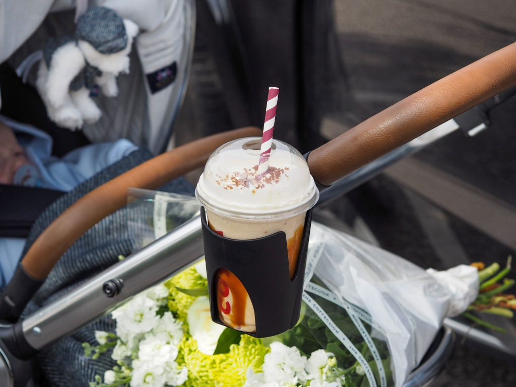 Close up of the Ocarro Moon pushchair's cup holder with an iced coffee inside.