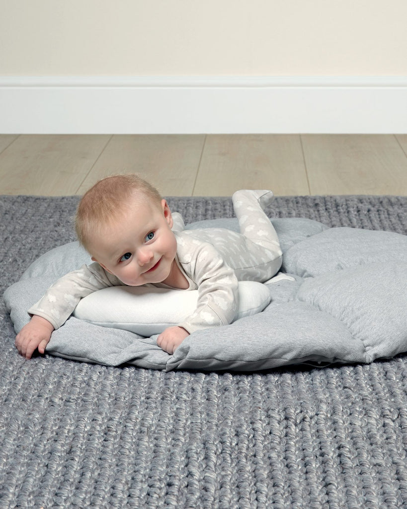 Image of a baby lying on their front on a Tummy Time playmat.