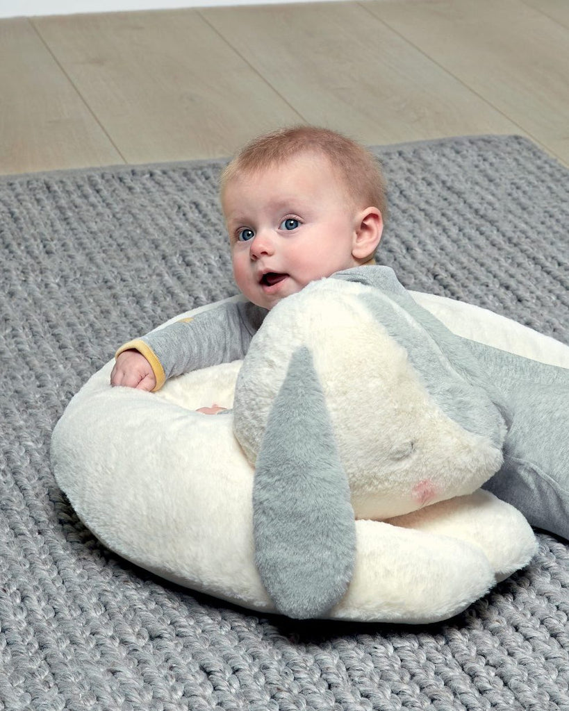 A baby lying on a rabbit-shaped Tummy Time pillow.
