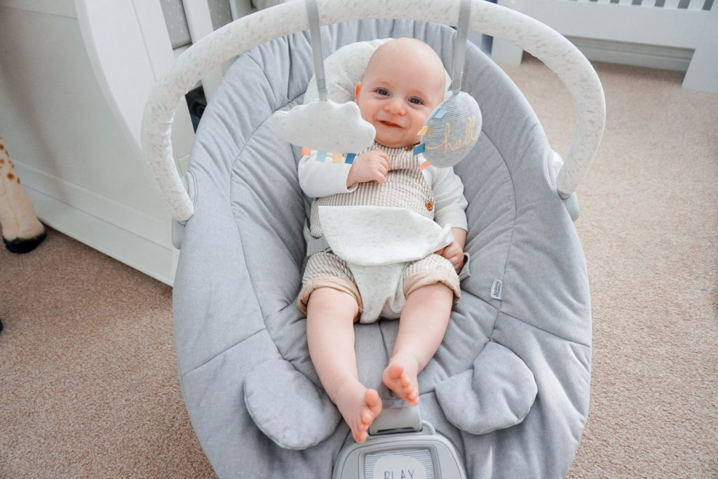Baby Theo is sat in his Apollo cradle, in the middle of a nursery. The cradle has a large plush looking seat and a handle that reached over him. Attached to the handle are two soft hanging toys.