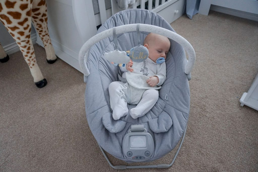 Another image of baby Theo asleep in the cradle, in the middle of a nursery. Behind thew cradle is a cot bed and dresser.