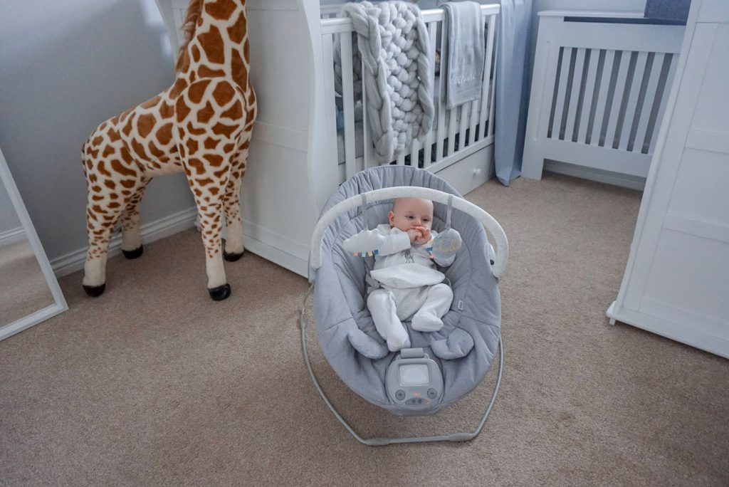 Baby Theo sat playing in his Apollo cradle in the middle of a nursery. Behind him is a cot, a mirror, a dresser changer and a large soft toy of a giraffe.