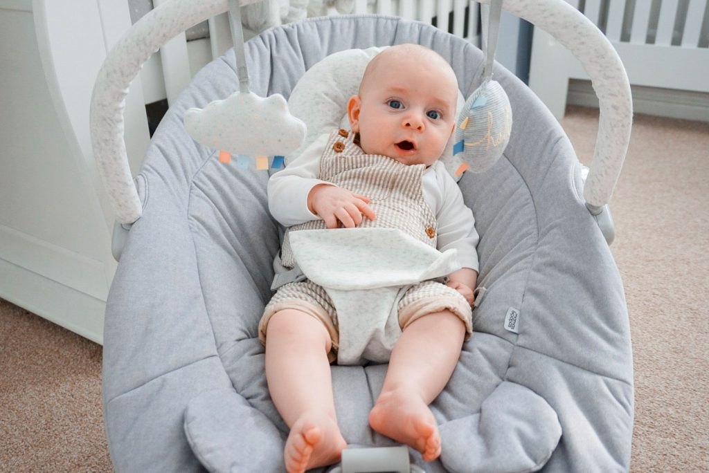 Another image of baby Theo sat in his Apollo cradle, playing. He is looking at the hanging toys.