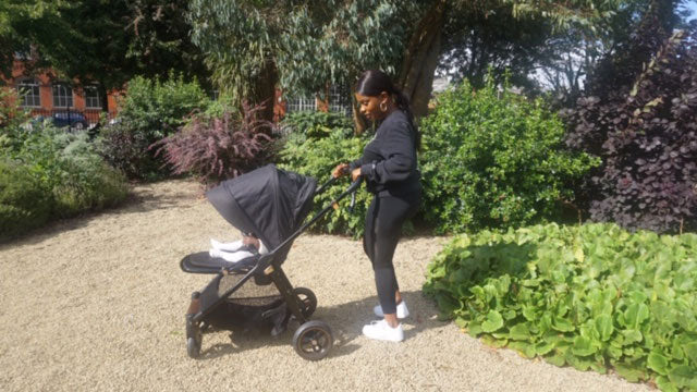 Parent Approved Panellist Danielle Lemonious is pushing the Flip XT Black Copper pushchair on a gravel path, through a garden with lots of bushes and shrubs.