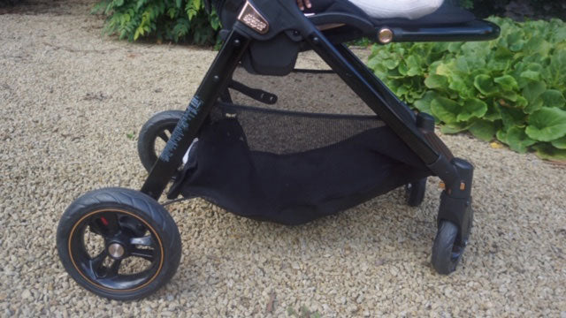 A close up of the wheels on the Flip XT3 Black Copper pushchair, showing the large wheels with copper trim details and a large shopping basket feature.