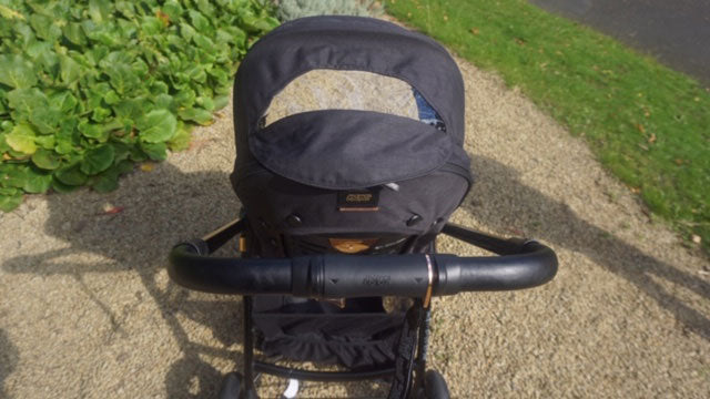 A close up of the Flip XT3 Black Copper pushchair hood and handlebar. The sun canopy on the hood is lower, revealing a gap through the hood that is covered with netting.