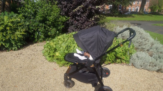 An image of baby Italia sat in the Flip XT3 Black Copper pushchair on a gravel path in a garden. The hood is up obscuring Italias face.