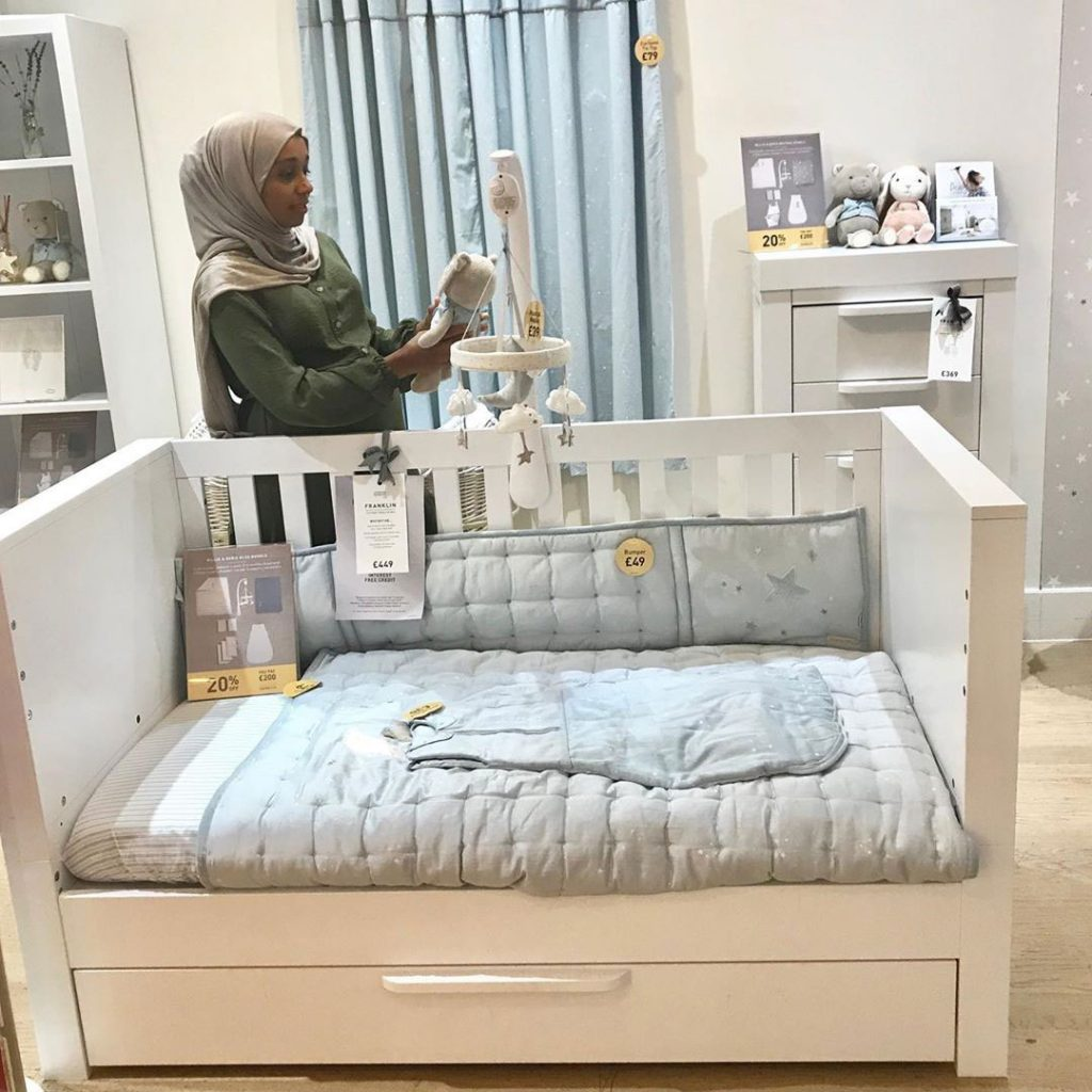 Parent Approved Panellist Salma Nuur is stood by a nursery furniture display. A cot bed is furnished with bedding, blankets and a cot mobile. Salma is looking at a soft toy.