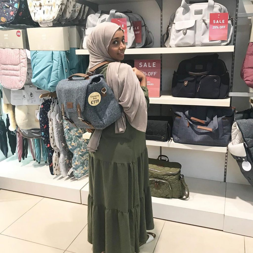 Parent Approved Panellist Salma Nuur is stood in a Mamas and Papas store in front of a display of changing bags. She is trying a changing bag rucksack on and posing for the camera.