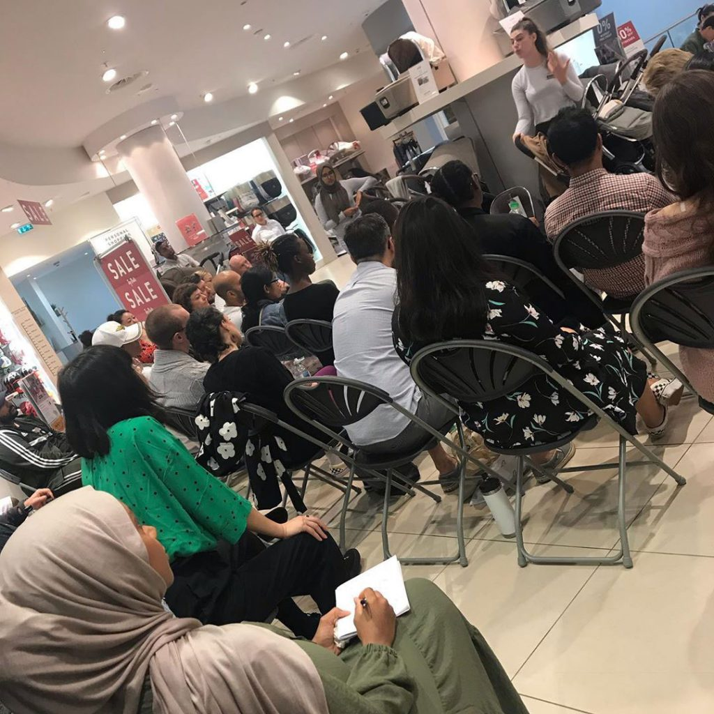 An image taken at a Parents to Be event, a group of expectant parents are sat around listening to a talk in a Mamas and Papas store. Some of them are taking notes.