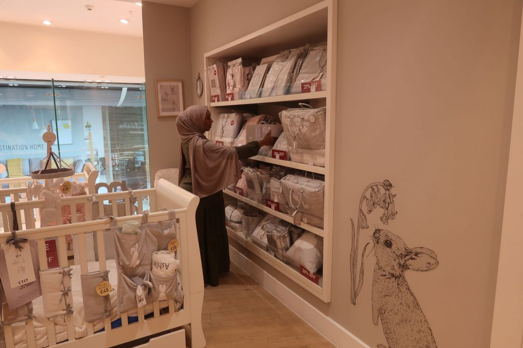 Parent Approved Panellist Salma Nuur is looking at a display of nursery soft furnishings in a Mamas and Papas store.