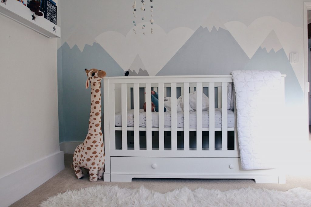 Image of the cot bed in a nursery, with a giraffe soft toy.