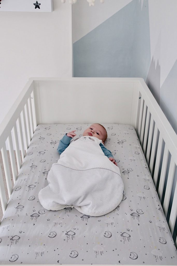 Image of Baby Gabriel in a sleep bag in the cot bed with the Dream Upon a Cloud bedding.