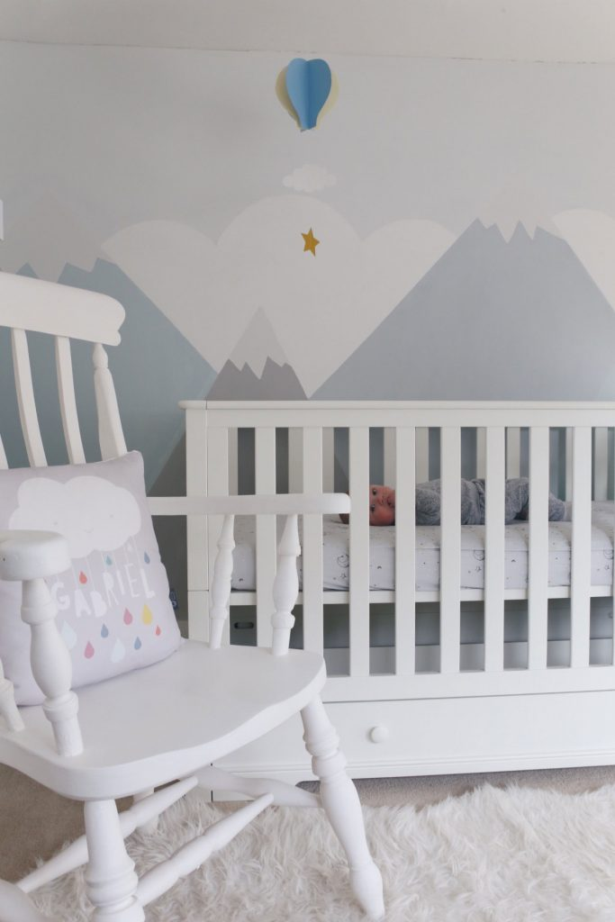 Image of the cot bed in a nursery next to a nursing chair.