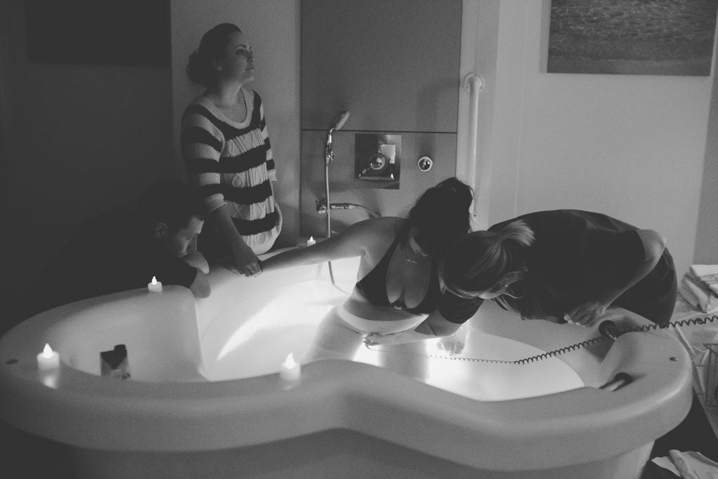 A pregnant woman is in labour, knelt in a birthing pool. Her partner and friends look on as a midwife monitors the baby's movements with an ultrasound.