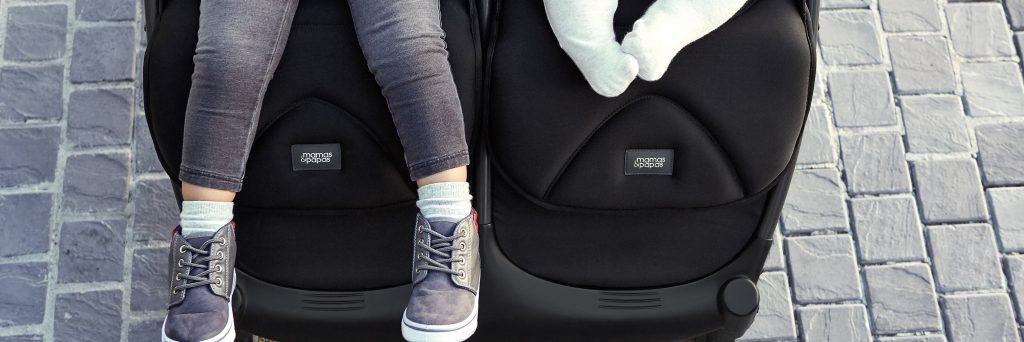 Close up of a twin pushchair, we can see the legs of an older child and the tiny legs of a baby.