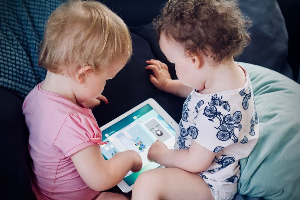 Two young children sit together on a sofa, playing with an ipad.