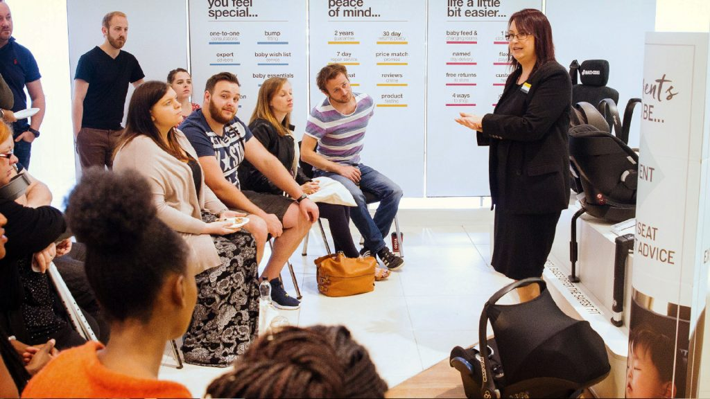 A woman is stood in a Mamas & Papas store in front of a crowd of people, addressing them and giving a speech on car seat safety. Behind her is an array of displays and informational graphics.