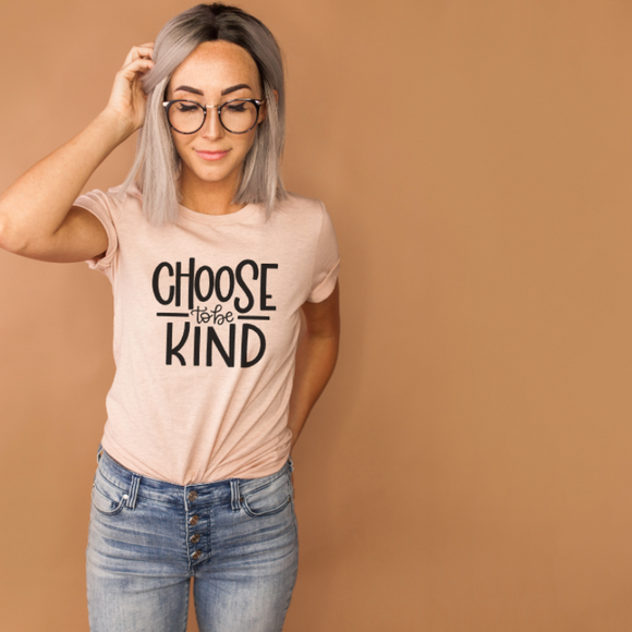 woman wearing peach shirt that reads Choose to be Kind