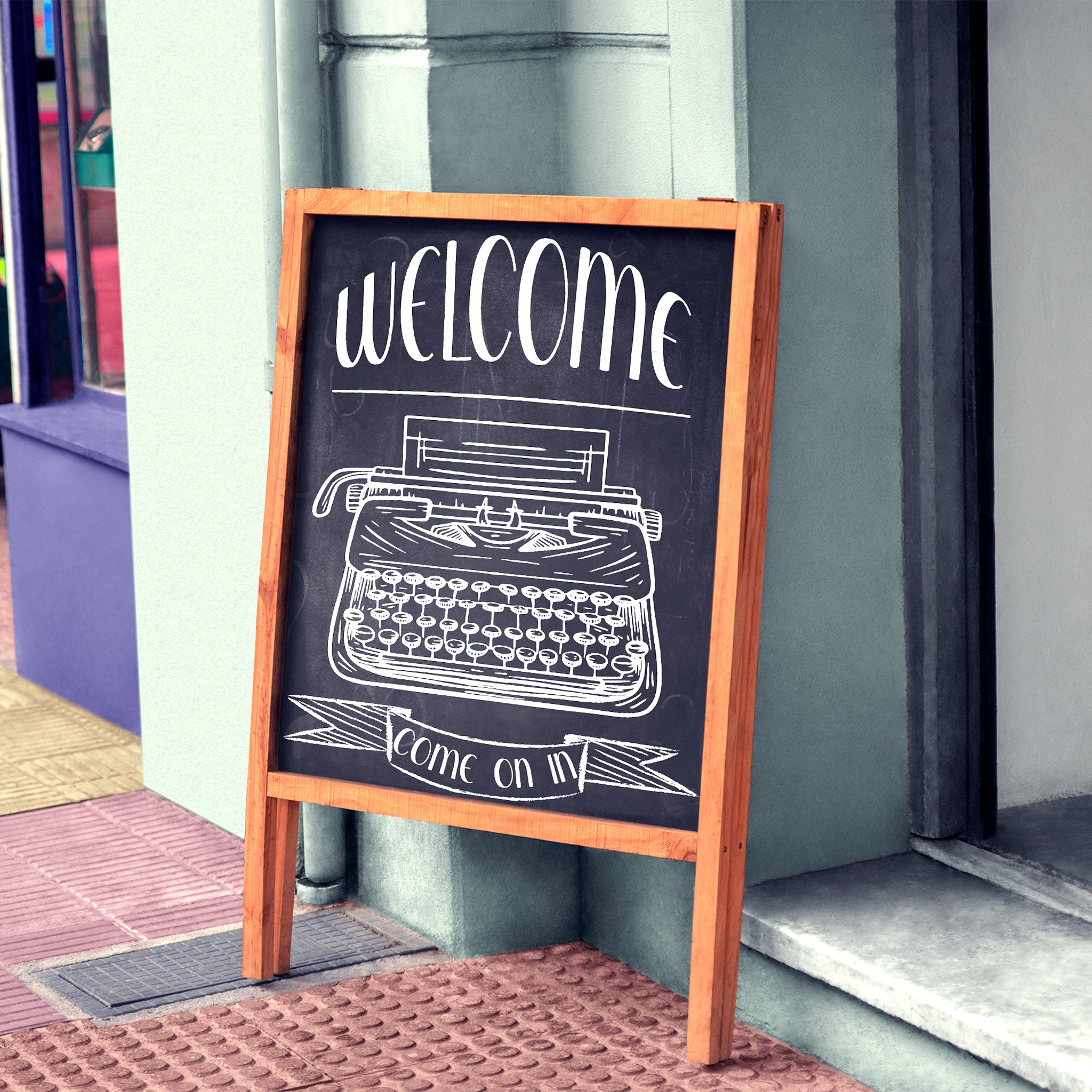 Shop chalkboard sign with white letters reading welcome com on in with a hand drawn picture of a type writer
