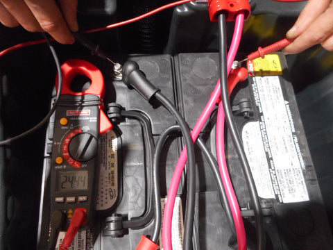 Checking voltage on floor scrubber battery pack using a volt meter.