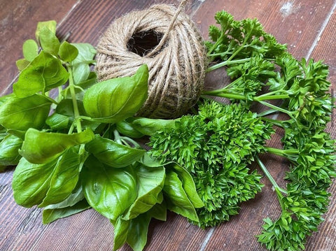 image of herbs and yarn ready to start drying on a wooden table