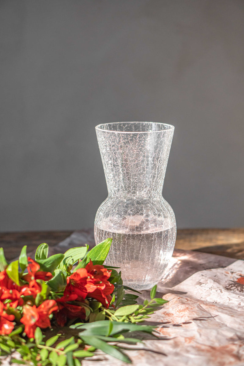 Crackle Crystal glass vase on a wooden table with red flowers next to it.