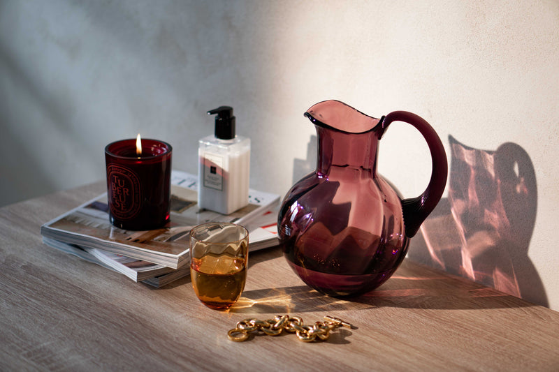 Violet Glass jug with Amber tumbler, magazines and candle on the table