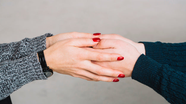 Cropped image of female psychologist holding her client's hands against gray backdrop Free Photo