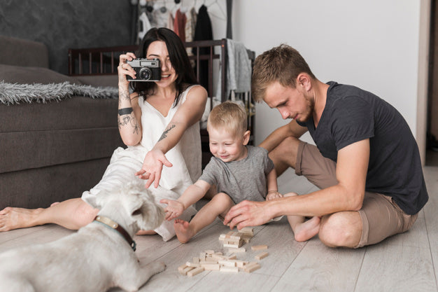 Young woman taking photo of dog with camera sitting near his son and husband playing together Free Photo